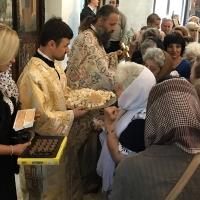 Раздаване на анафора и почерпка от съпругата на новия дякон (вляво)